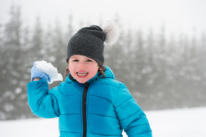 Cute little boy in blue jacket and hat playing outside in snow in winter nature, throwing snow ball, smiling